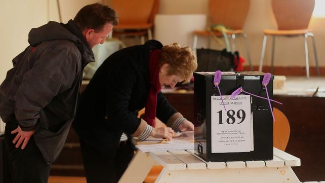 Presiding Officer Carmel McBride checks the name of a voter (left) on Inis Bó Finne