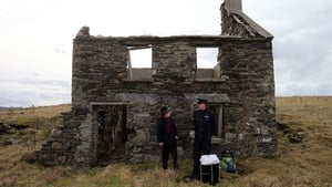 Presiding Officer Carmel McBride and Garda Sergeant Paul McGee stand with a ballot box outside an abandoned home on the island of Inishbofin, Co Galway, awaiting the arrival of a helicopter to take them back to the mainland
