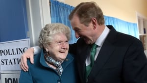 Taoiseach Enda Kenny meets Bridie McLoughlin on her 88th birthday after they both cast their votes at a polling station at St Anthony's School in Castlebar, Mayo