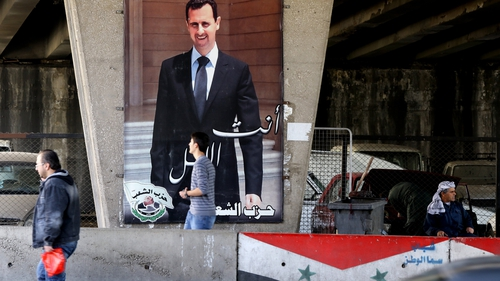 Syrian men walk past a poster bearing a portrait of President Bashar al-Assad in Damascus