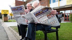 Fianna Fail officials read the morning newspapers as they wait outside the count centre in Dublin