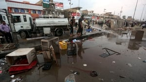 Iraqi men clean up the site following the bombing near a market in the Sadr City area of northern Baghdad