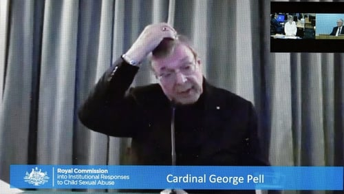 Cardinal George Pell is shown on a screen in Canberra, as he gives evidence to the commission via video link from Rome