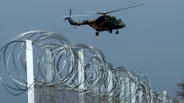 A police helicopter flies over the fence on the Greece/Macedonia border line