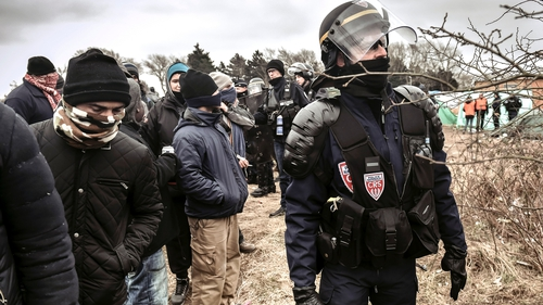 Policemen stand next to agents dismantling shacks as refugees look on in the 'Jungle' camp