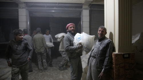 Syrians unload an aid delivery in the rebel-held town of Sabqa