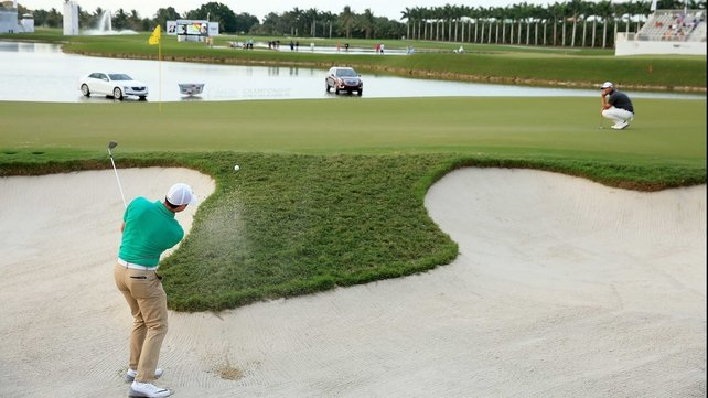 Rory McIlroy escapes from the bunker on 17