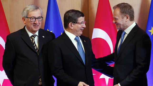 EC President Jean-Claude Juncker, Turkey's Prime Minister Ahmet Davutoglu and European Council President Donald Tusk talk as they arrive for the EU leaders summit