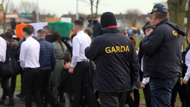 A number of men in white shirts and black ties escorted Vincent Ryan's coffin as gardaí looked on