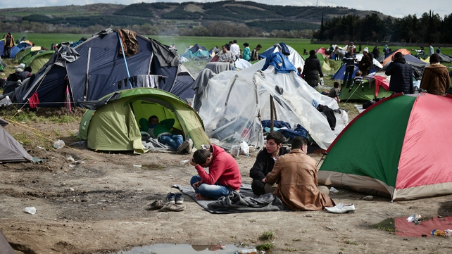 People sit in a makeshift camp at the Greek-Macedonian borders