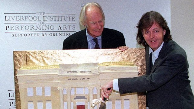Paul McCartney cutting a giant cake modelled on the Liverpool Institute for Performing Arts, watched by George Martin in 1996