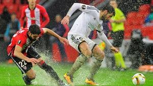 Athletic Bilbao midfielder Raul Garcia (L) vies with Valencia's Argentinian midfielder Enzo Perez on a soaked Estadio de San Mames pitch