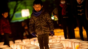 A boy walks past the paper lanterns at Natori City Office