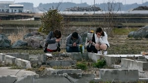 Toshiaki Fujita (2-L) offers a prayer for his late mother Toshiko, who was killed five years ago