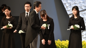 Japanese PM Shinzo Abe (C) holds a chrysanthemum as an offering for the victims of the earthquake and tsunami
