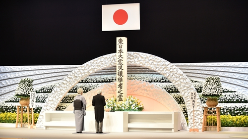 Emperor Akihito with Empress Michiko deliver an address in front of an altar for the victims