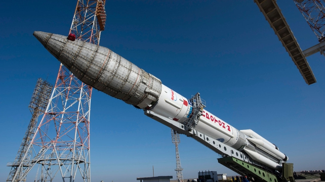 A view of the Proton rocket as it is rolled out from a fueling station during its transfer to the pad of the launch complex at the Baikonour spaceport, Kazakhstan