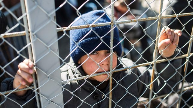 A child looks through a fence as migrants from Syria wait to cross the Greece-Macedonia border near the town of Gevgelija
