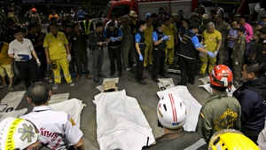 Covered bodies of victims lie next to forensic police officers and rescue workers