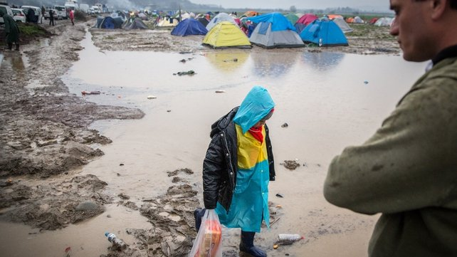 People walk beside tents close to standing water that has developed due to heavy rain fall at the Idomeni refugee camp