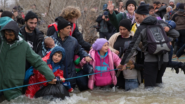 The people used a rope to help them cross a swollen river