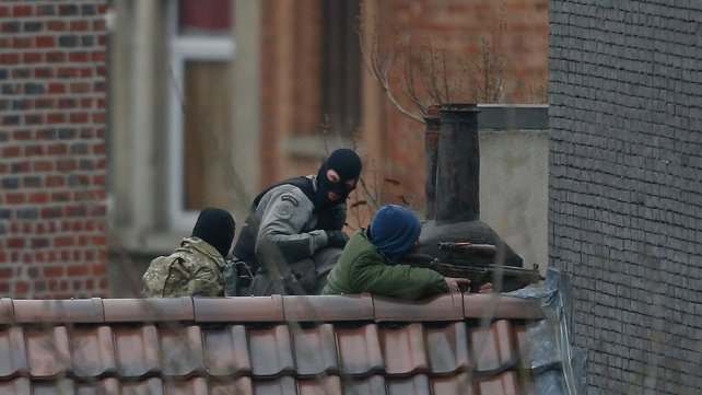 Police officers take position on a rooftop during a police operation in Brussels today