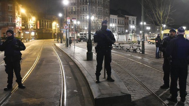 Officers stand in position on the site where shots were fired in the southern Forest district of Brussels