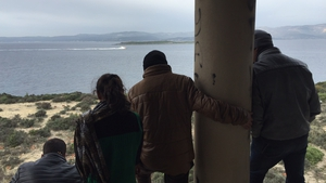 People gaze across the narrow strait of water separating Turkey from the Greek island of Chios, clearly visible on the horizon