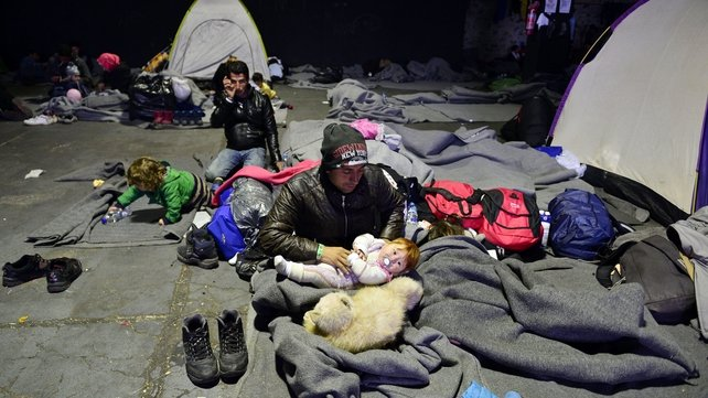 An Iraqi family rests in a warehouse at the port of Piraeus near Athens where thousands of refugees and migrants find temporary shelter