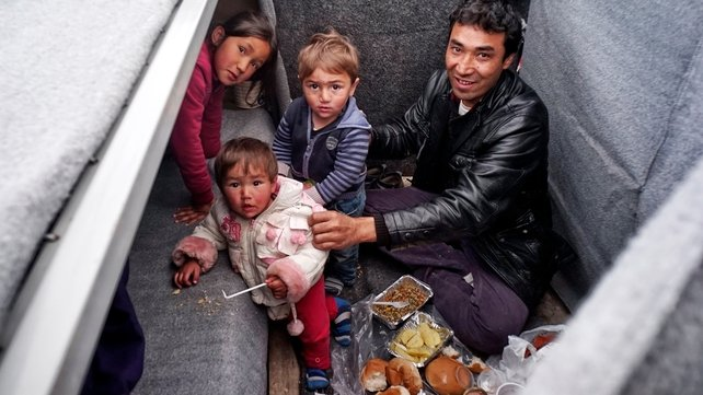 Families separate their beds and living space with blankets in a UNCHR tent at a refugee camp in the western Athens suburb of Schisto