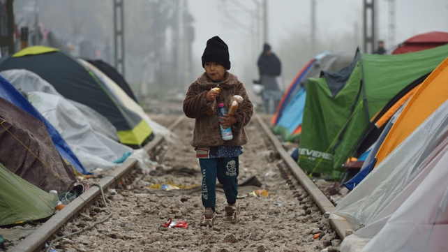A child eats as he walks through tents installed on railroad tracks, at a makeshift camp of the Greek-Macedonian border