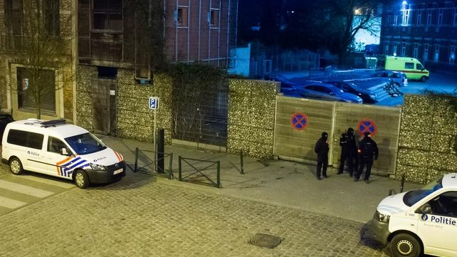 Belgian police wait in a street outside the sealed-off area in Molenbeek