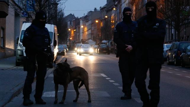 Belgian police guard the sealed-off area in the Molenbeek neighborhood of Brussels