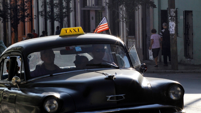 A taxi with a US flag is seen on the streets of Havana, Cuba