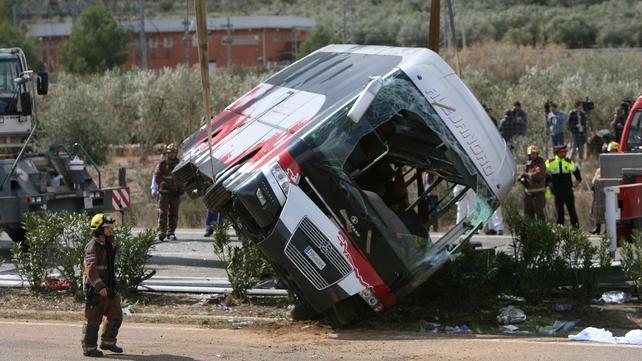 Firemen work at the site of the bus crash in Tarragona, northeastern Spain