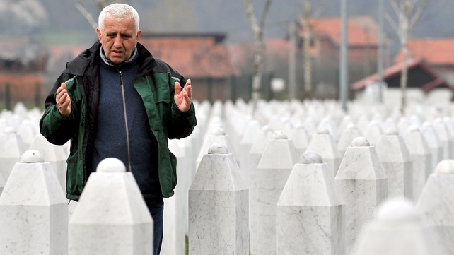 A survivor of the massacre in Srebrenica prays by his relatives' graves after the guilty verdict