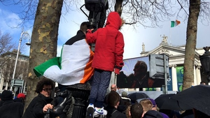Children climb a lamppost for a better view of the parade