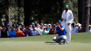 Jordan Spieth and caddie Michael Greller line up a putt on the sixth