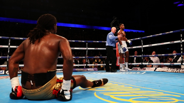 Anthony Joshua is ordered back to his corner by the referee as Charles Martin sits on the canvas