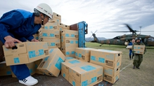 Relief personnel unload boxes of bottled water from a military helicopter after the second major earthquake hit Aso city, Kumamoto