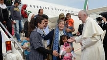 Pope Francis welcomes the group of Syrian refugees that flew with him after landing at Ciampino airport in Rome this afternoon