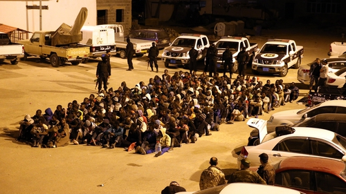 Migrants are stopped from attempting a Mediterranean crossing after a police raid on their hideout in Tripoli, Libya