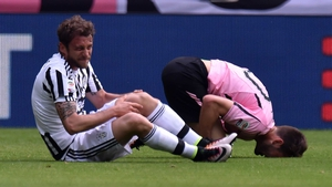 Claudio Marchisio clutches his left knee after falling awkwardly