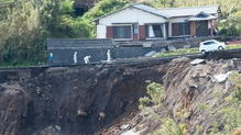 A house teeters on a mountainside following a major landslide caused by the earthquakes in Kumamoto