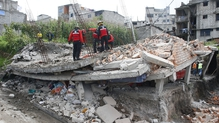 Rescue workers search for people in the rubble