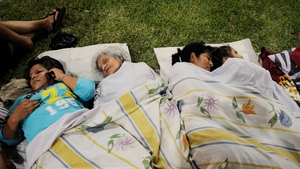 People rest in a park in Guayaquil after the earthquake destroyed buildings and sent people running from their homes