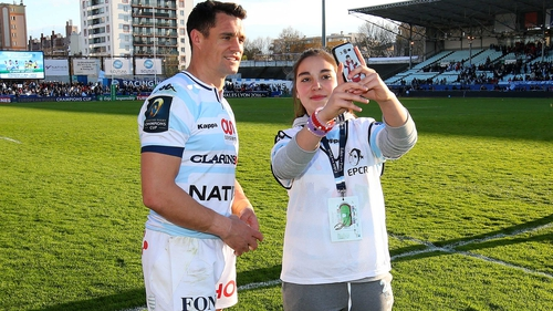 Caster poses with a young fan following a Racing 92 match