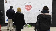 Passengers read messages on a commemorative wall at Maalbeek metro station
