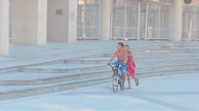 Boys cycle in front of the Maracana stadium