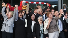Relatives of those who died sing 'You'll never walk alone' following the inquest